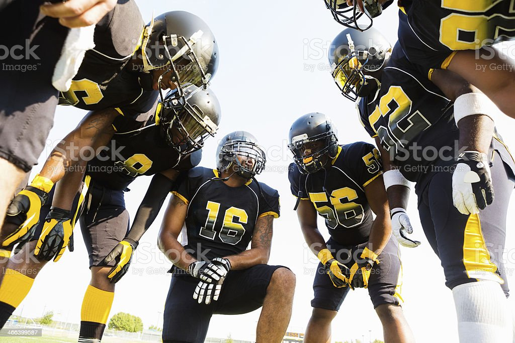 Football team huddled during time out while playing game stock photo