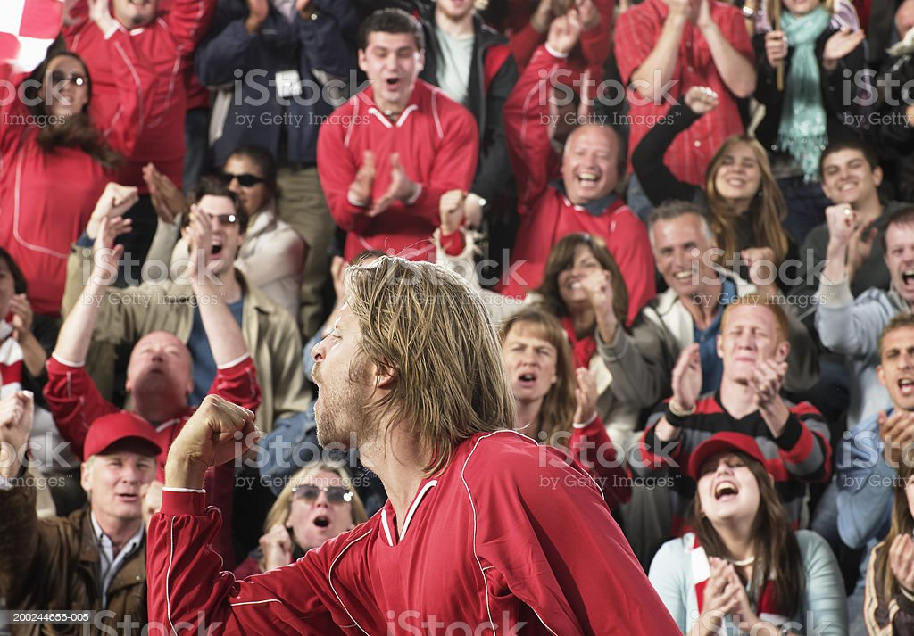 Footballer celebrating in front of cheering crowd, side view royalty-free stock photo