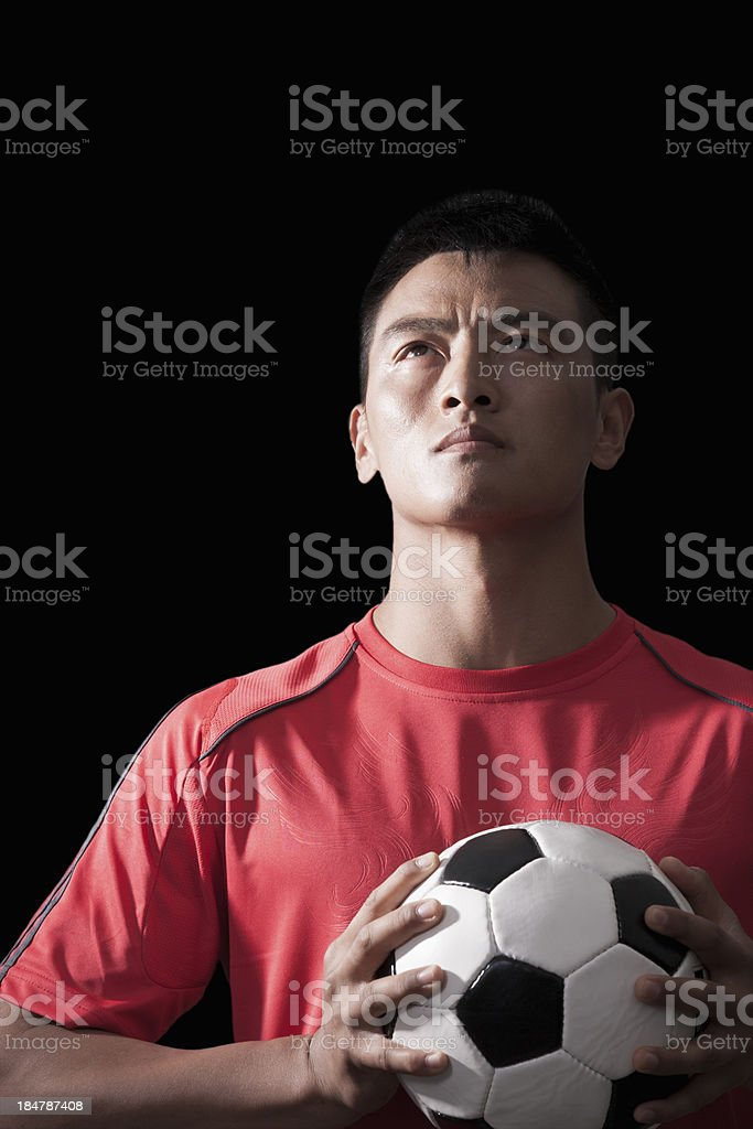 Footballer holding ball to chest, black background royalty-free stock photo