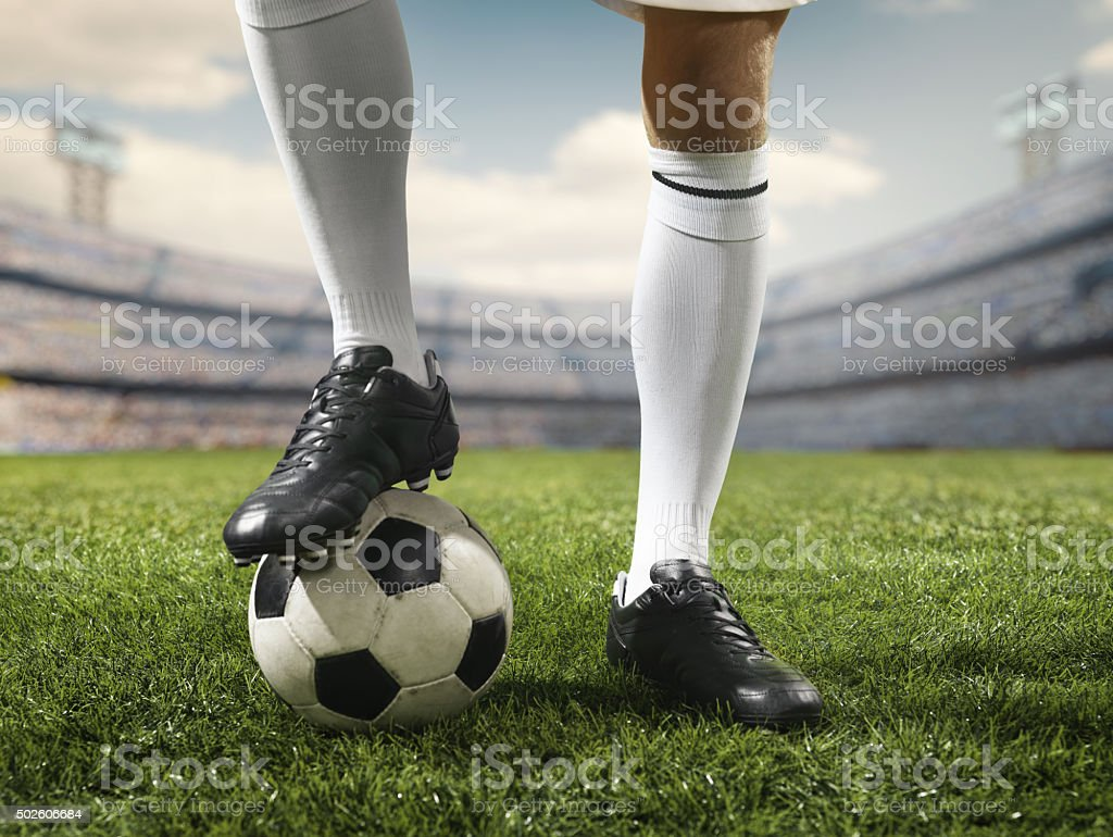 Footballer leg on a soccer ball stock photo