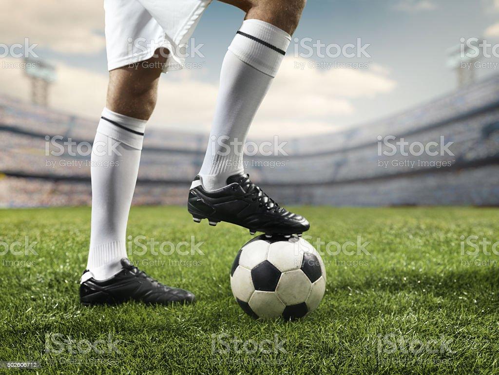 Footballer leg on a soccer ball stock photo