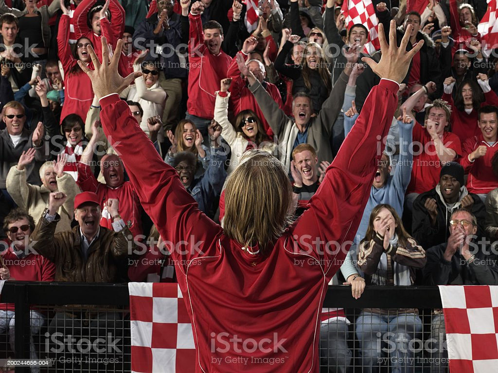 Footballer raising arms in front of cheering crowd, rear view royalty-free stock photo