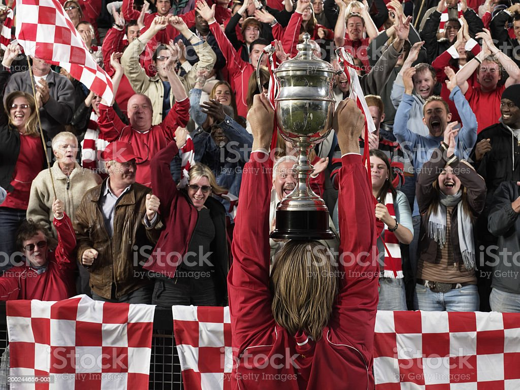 Footballer raising trophy above head in front of cheering crowd royalty-free stock photo