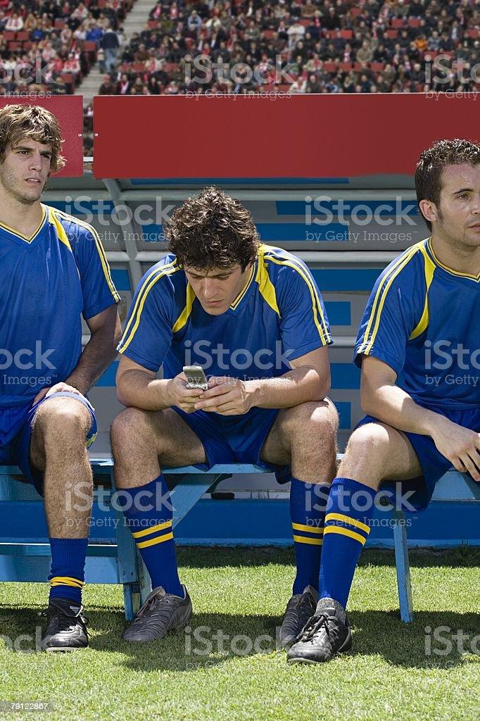 Footballer using cell phone stock photo
