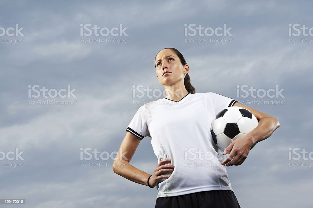 Fu?ballerin mit Fu?ball vor Himmel stock photo