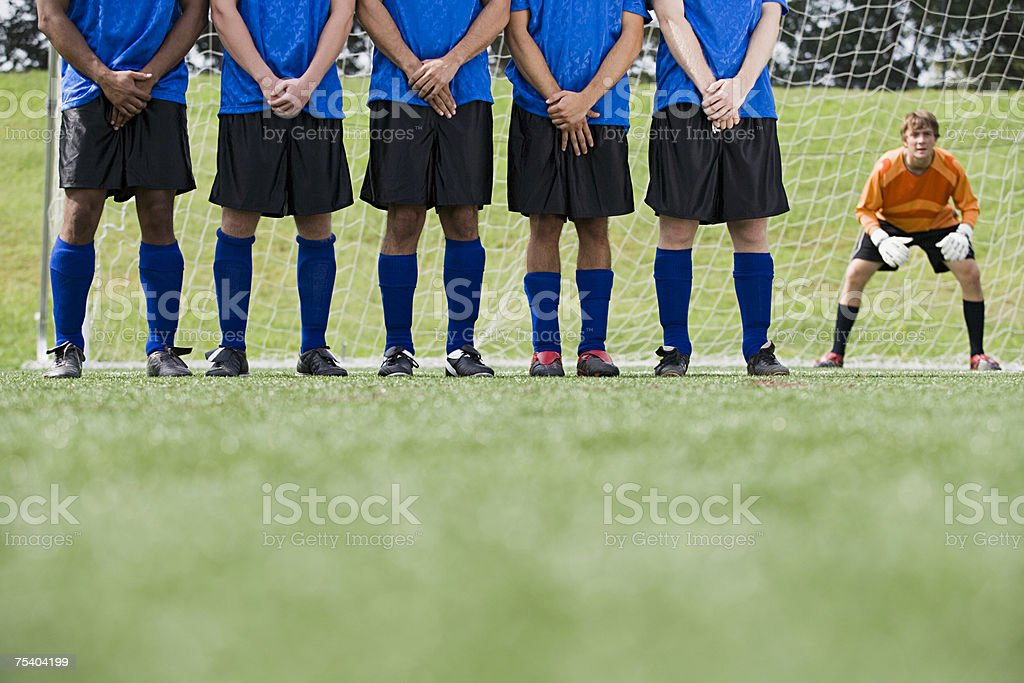 Footballers and goalkeeper royalty-free stock photo