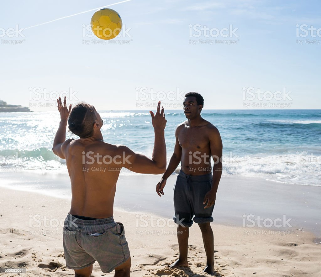 Footballers playing headers at the beach stock photo