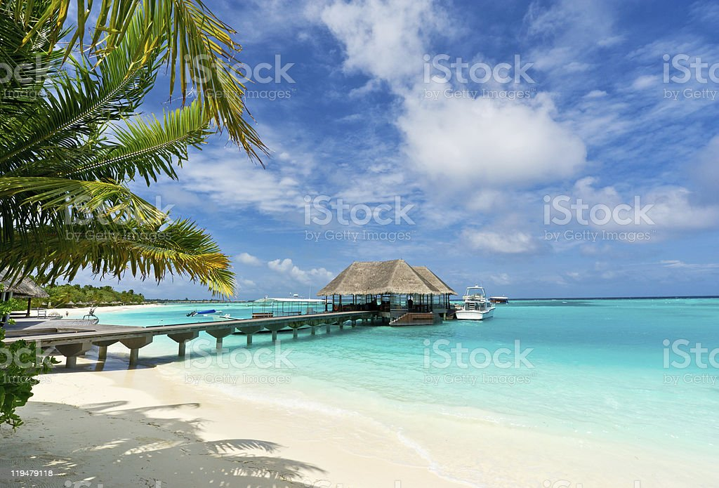 footbridge connecting with thatched jetty in maldives resort stock photo