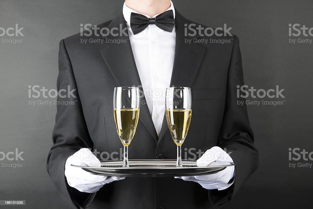 Footman in black holding tray with two glasses of white wine royalty-free stock photo