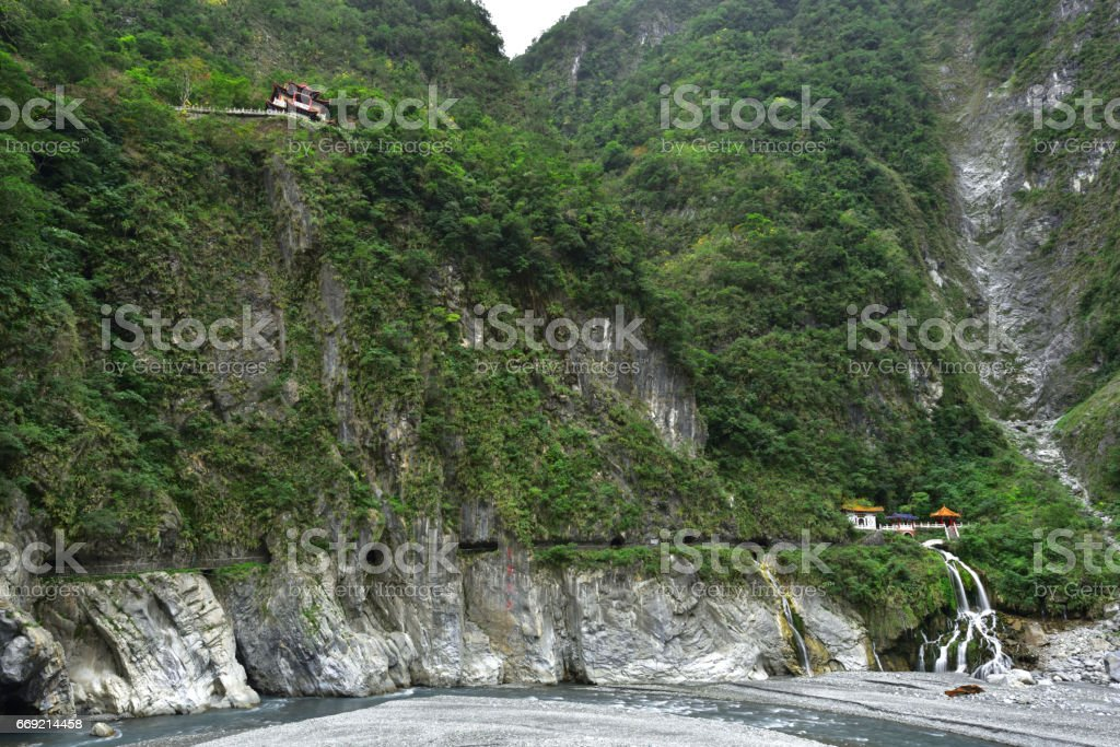 Footpath and tunnel pass through perpendicular cliff and mountain valley stock photo