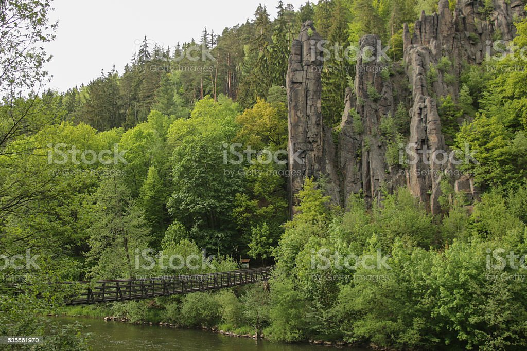 Footpath over a river, forest and rocks stock photo
