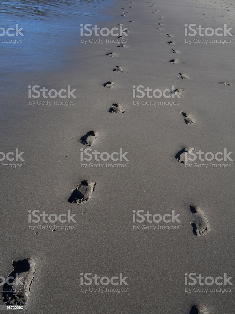 Footprints along otherwise smooth sand at Rialto Beach stock photo