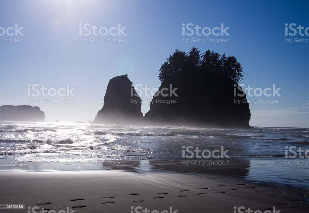 Footprints along Rialto Beach, with Silhouetted Islands and Brig stock photo