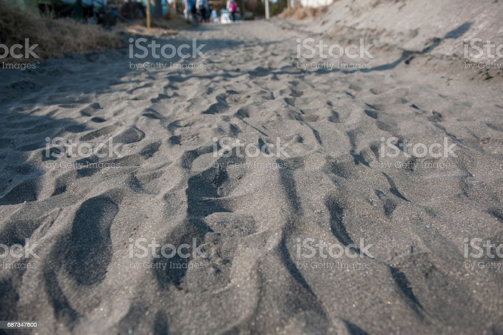 Footprints in black sand stock photo