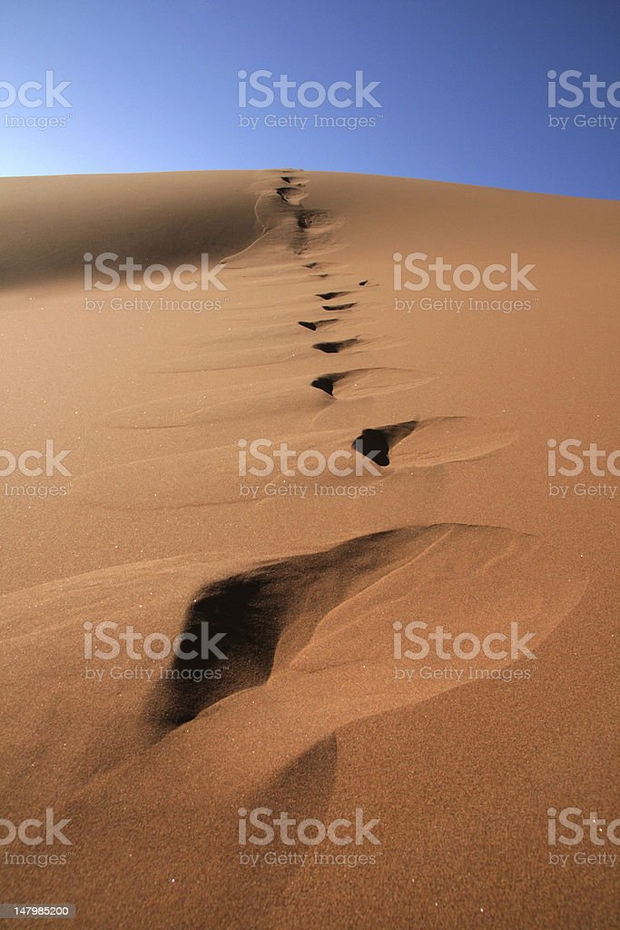 Footprints in red sand dune stock photo