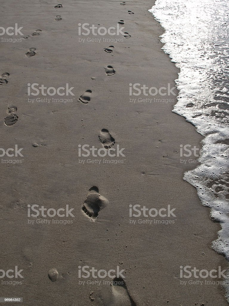 Footprints in sand at surf line lead toward camera. stock photo
