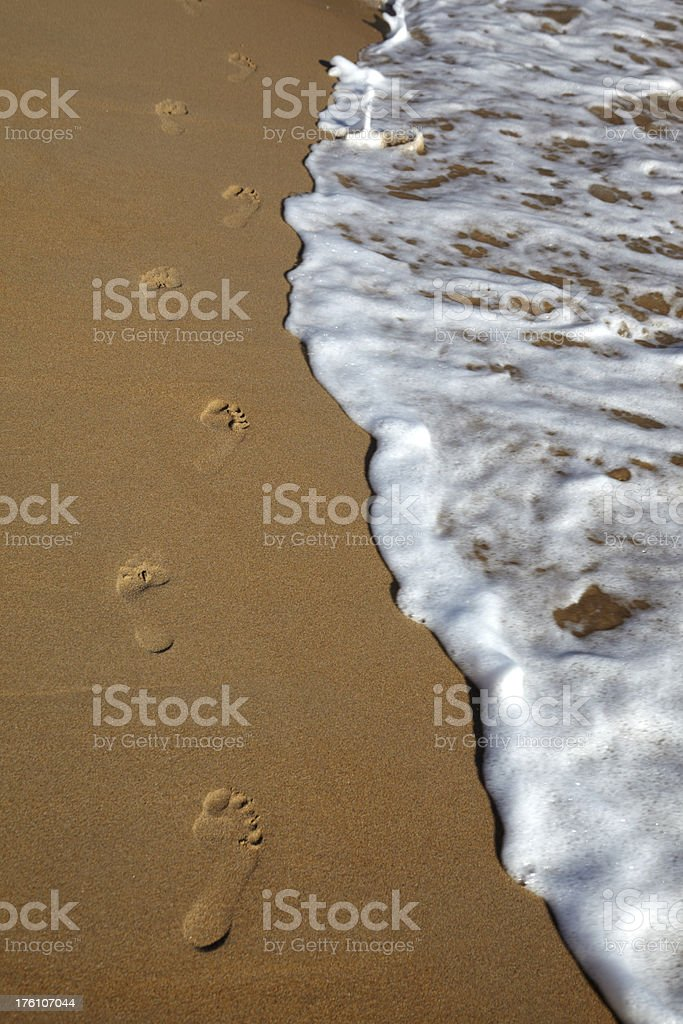Footprints in sand on beach with wave royalty-free stock photo