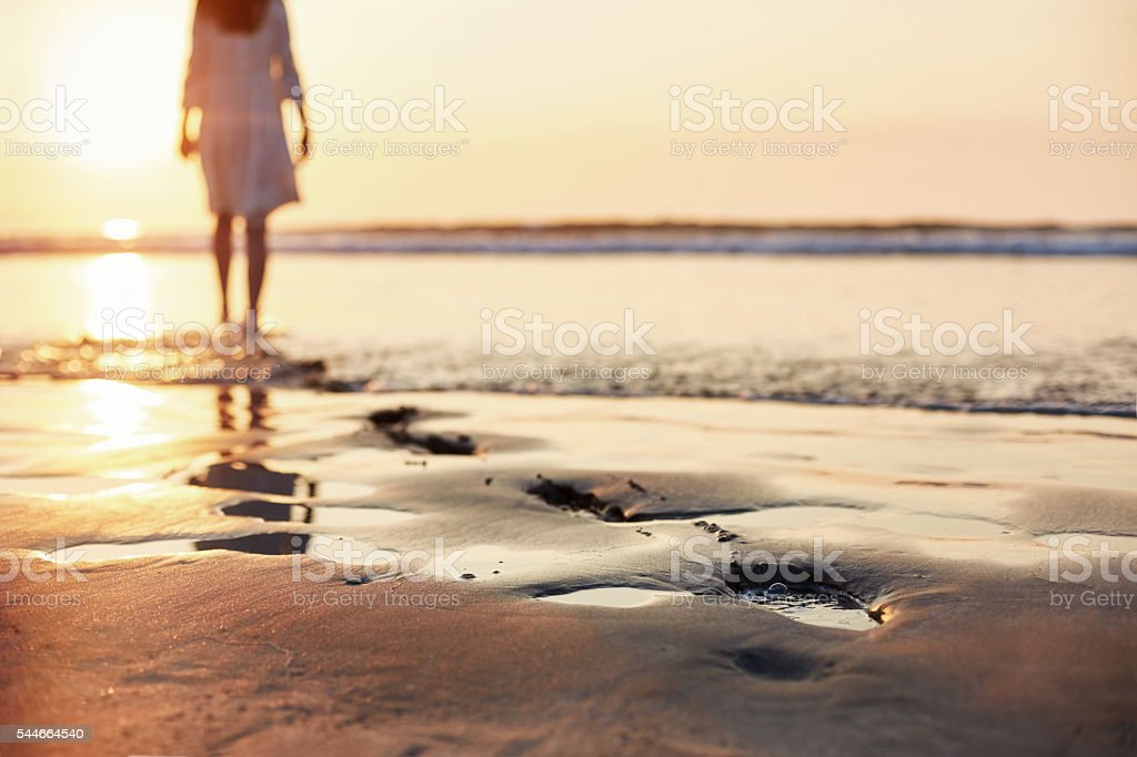 Footprints in sand with woman walking in background during sunse stock photo