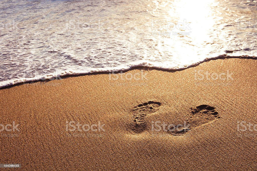 Footprints in the sand along the shoreline stock photo