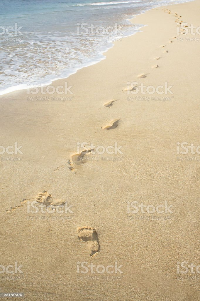 Footprints in the sand on the beach. stock photo
