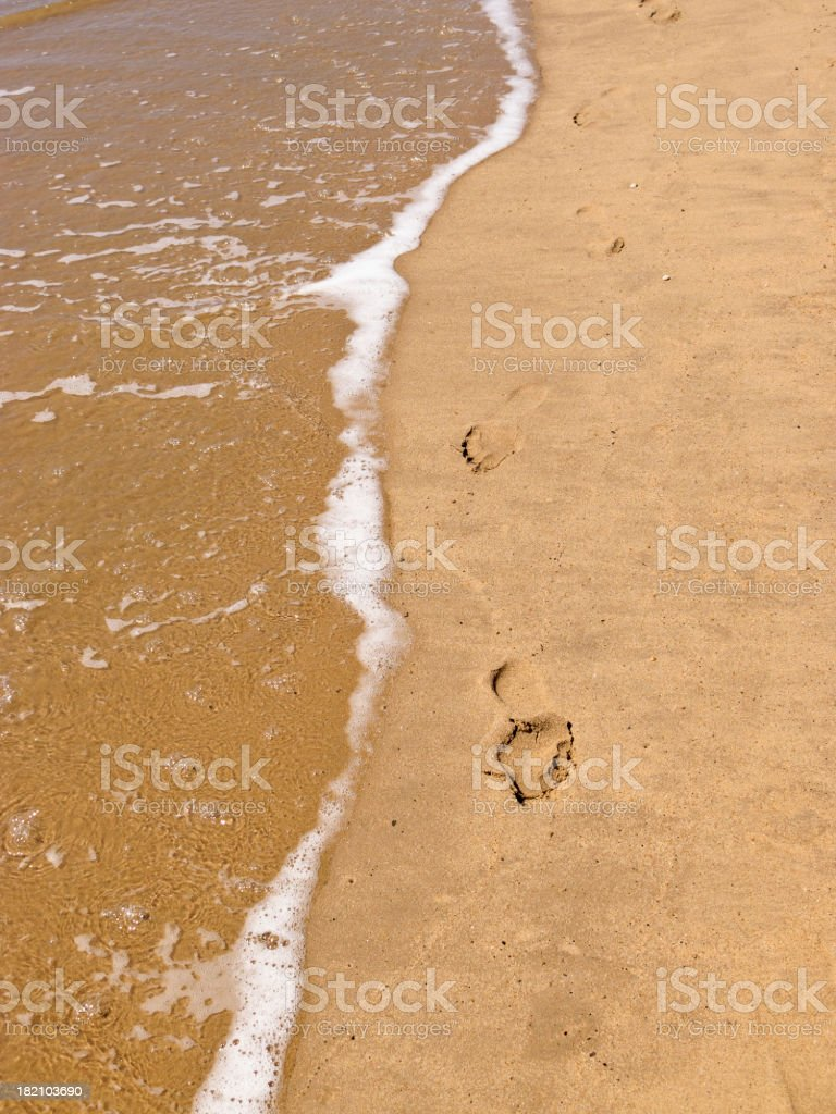 Footprints in the sand on waters edge royalty-free stock photo