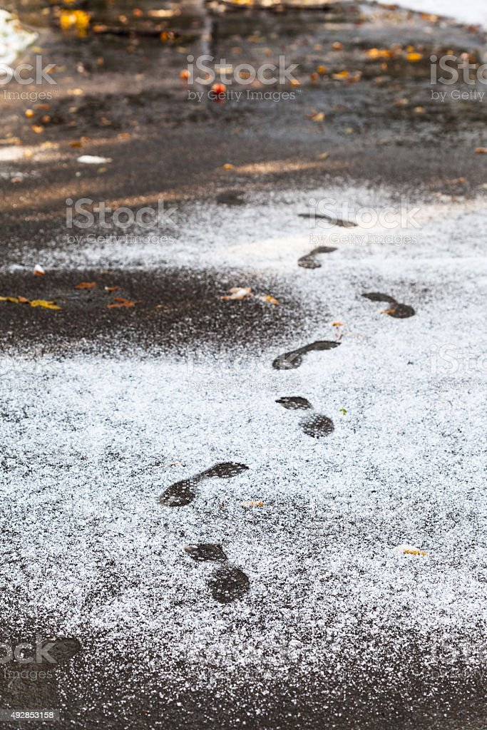 footprints in wet path covered by first snow stock photo