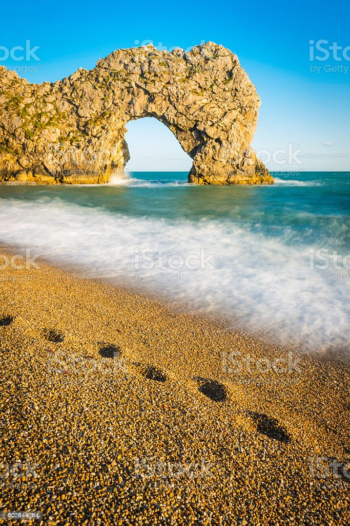 Footprints on the beach blue ocean rock arch white surf stock photo