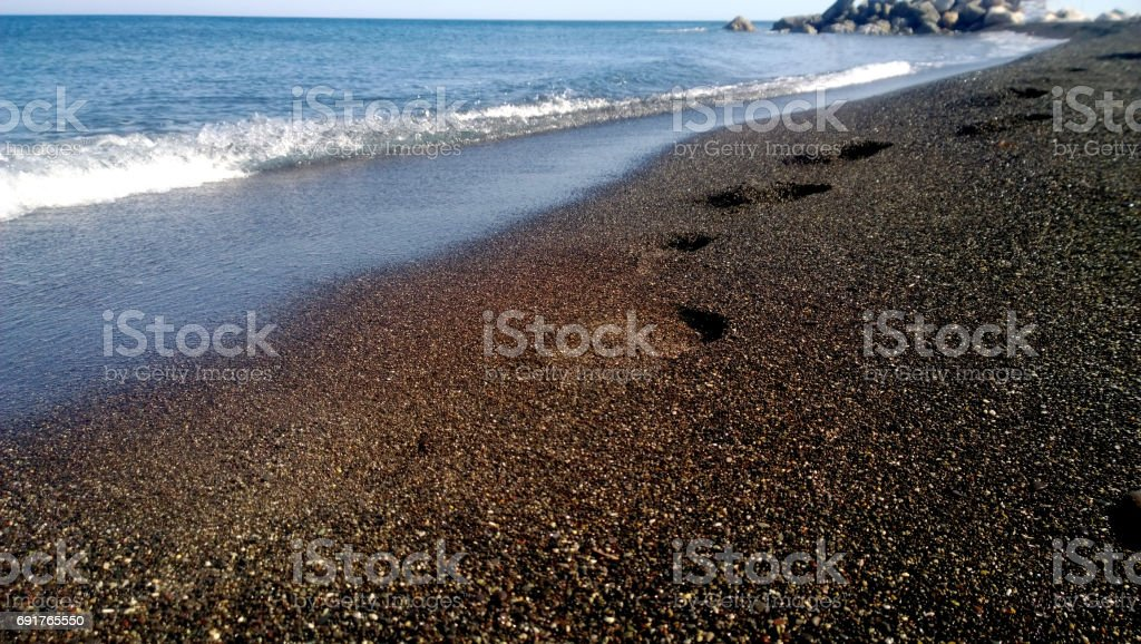 Footprints on the sea shore on the black sand. Sea wave in the background stock photo