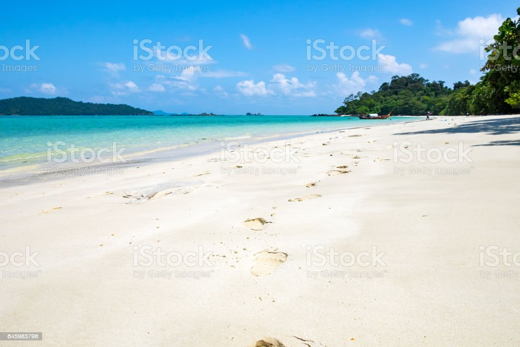 Footprints on white sand and crystal sea stock photo