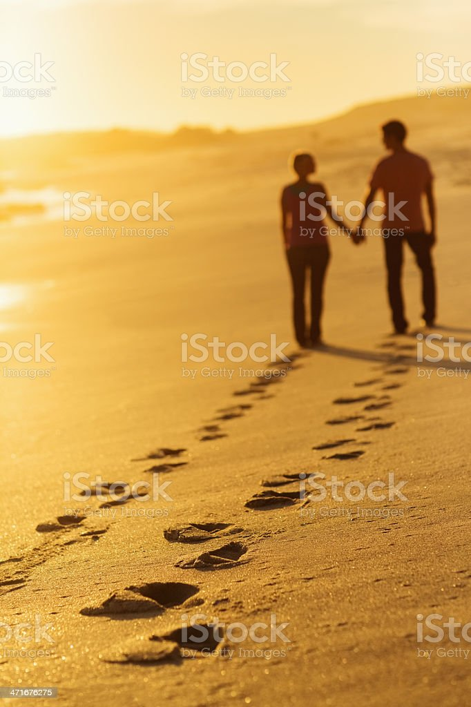 Footprints Track With Couple Walking On Beach At Sunset royalty-free stock photo