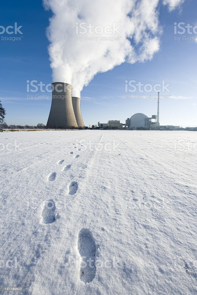 Footsteps in snow towards nuclear power station (XXL) royalty-free stock photo