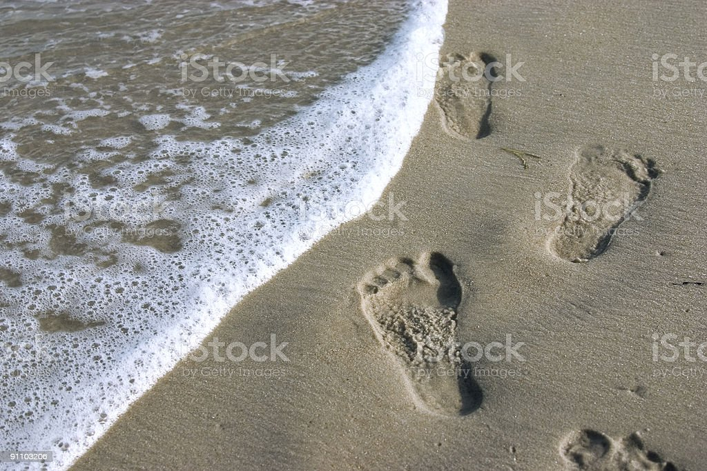 Footsteps on beach stock photo
