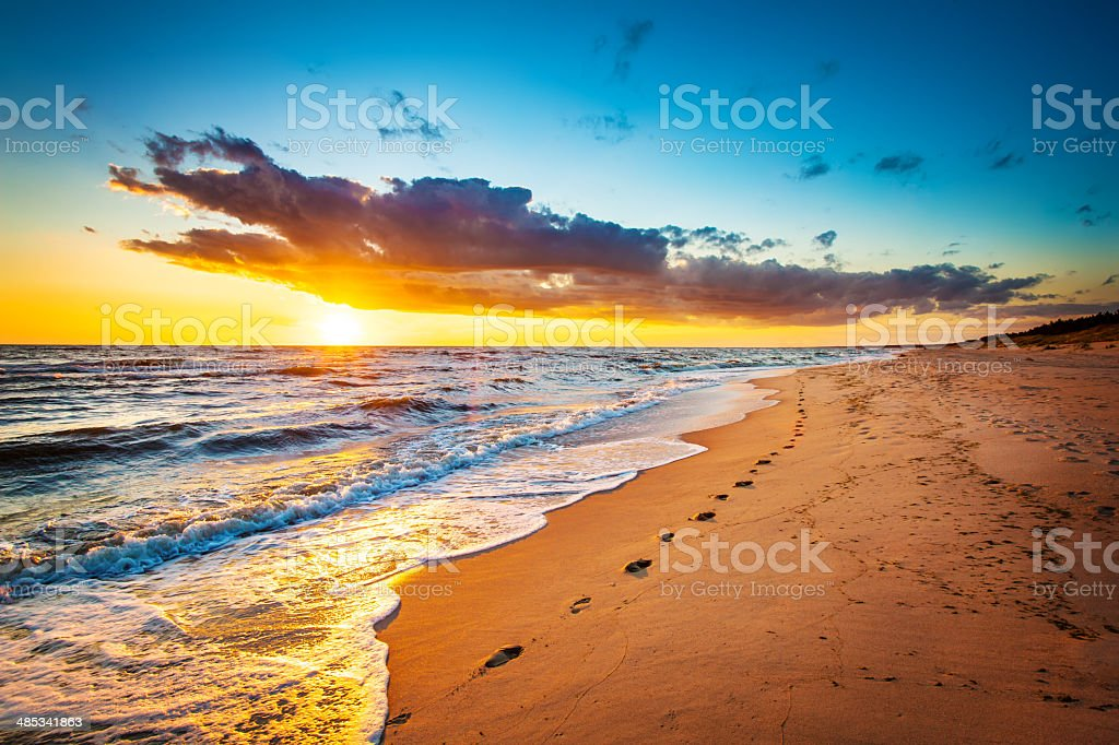Footsteps on the Sand - empty Beach during Sunset. stock photo