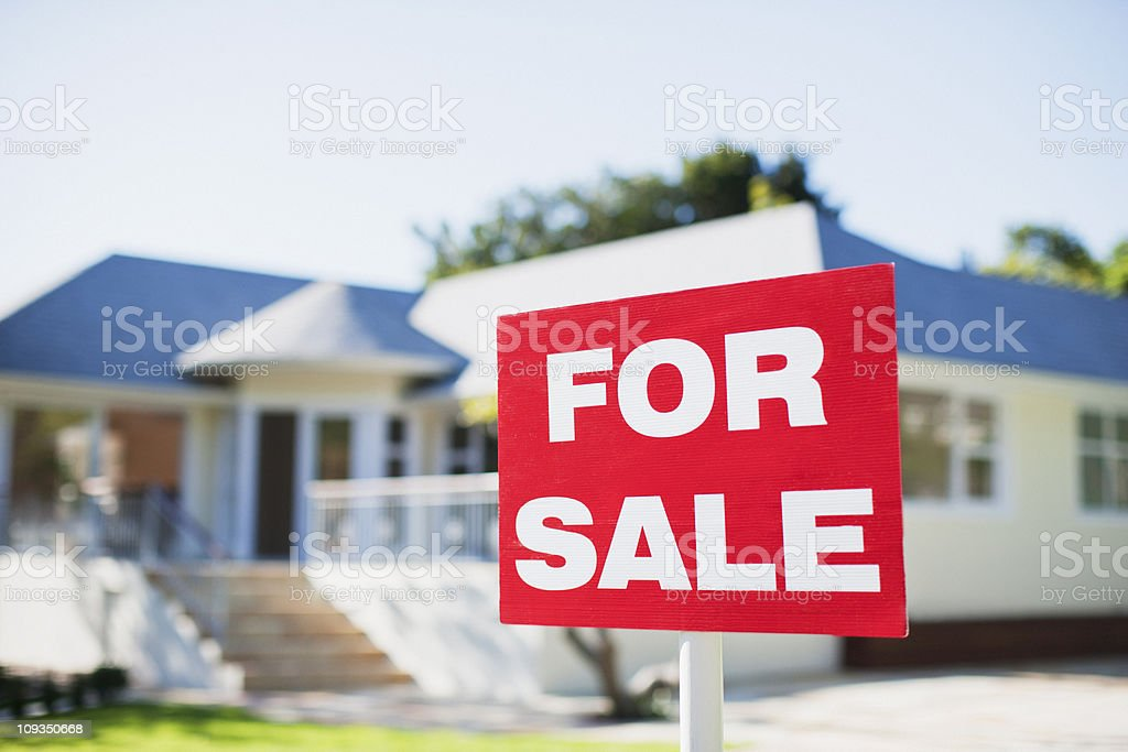 For sale sign in yard of house stock photo