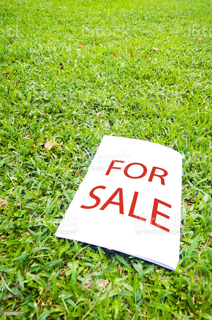 For sale sign laying in green grass royalty-free stock photo