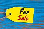 For Sale tag on blue wooden background. Sales, discount, advertising