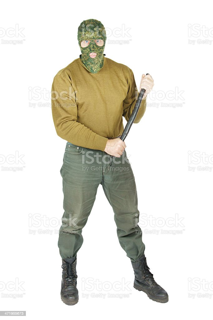 Forceful man wearing a camouflag mask holds rubber club stock photo