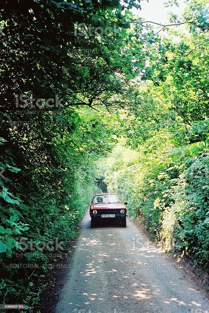 1978 Ford Escort driving along leafy English lane stock photo