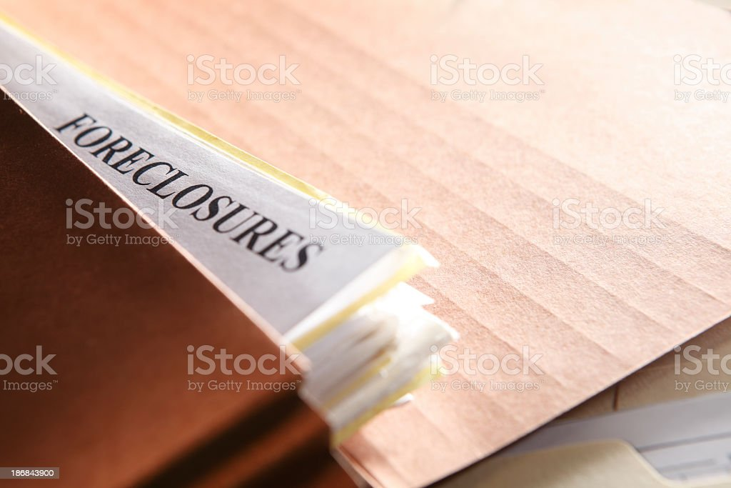 Foreclosure documents stuffed into a brown file folder stock photo