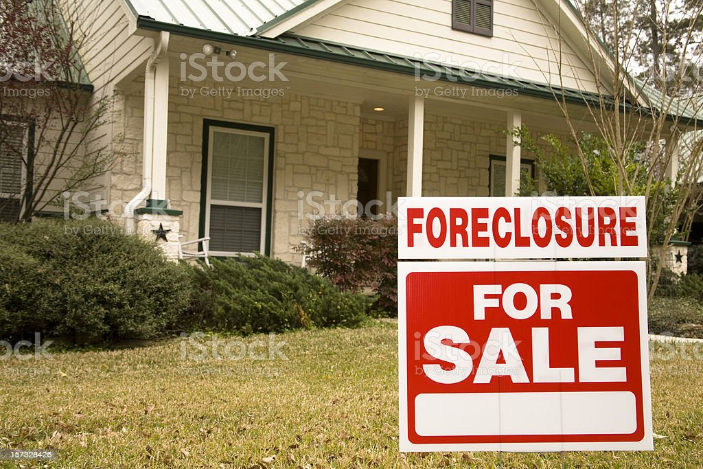 Foreclosure for sale sign in front of house stock photo