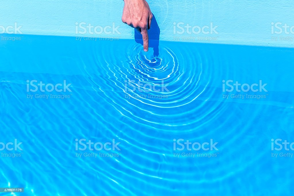 Forefinger making circular waves in swimming pool stock photo