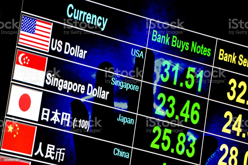 foreign currency exchange rate board with lighting hand in backg stock photo
