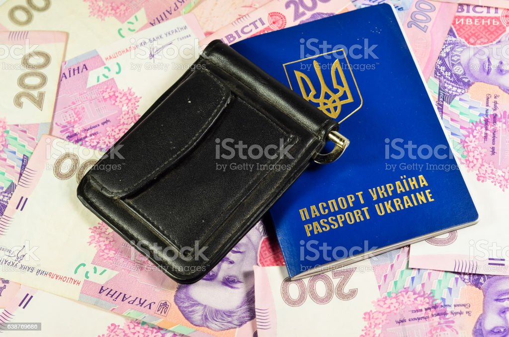 Foreign passport and money clip on background of ukrainian banknotes stock photo