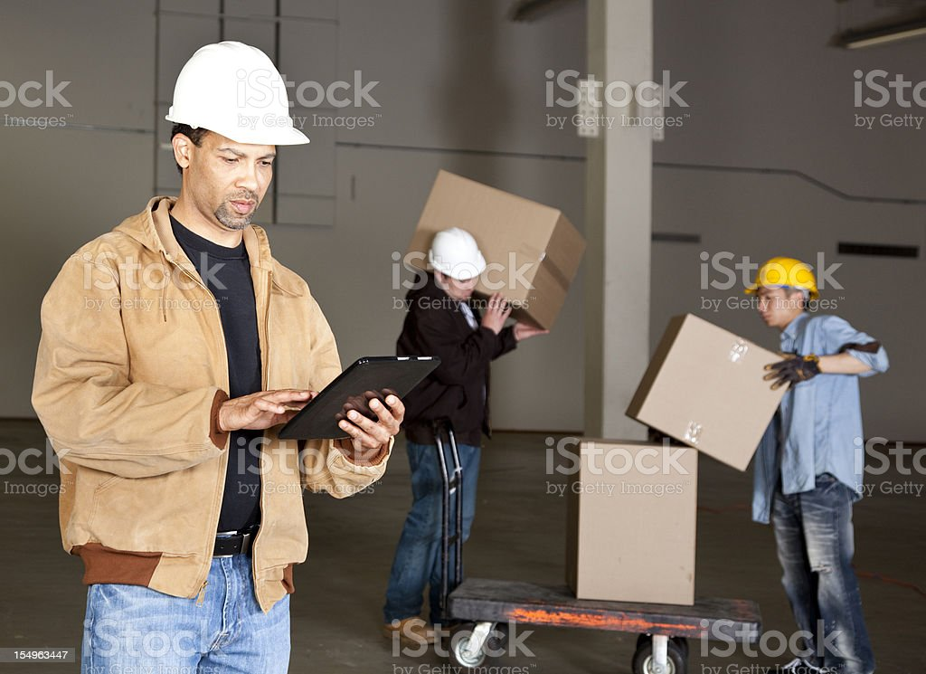 foreman and manual workers in warehouse royalty-free stock photo