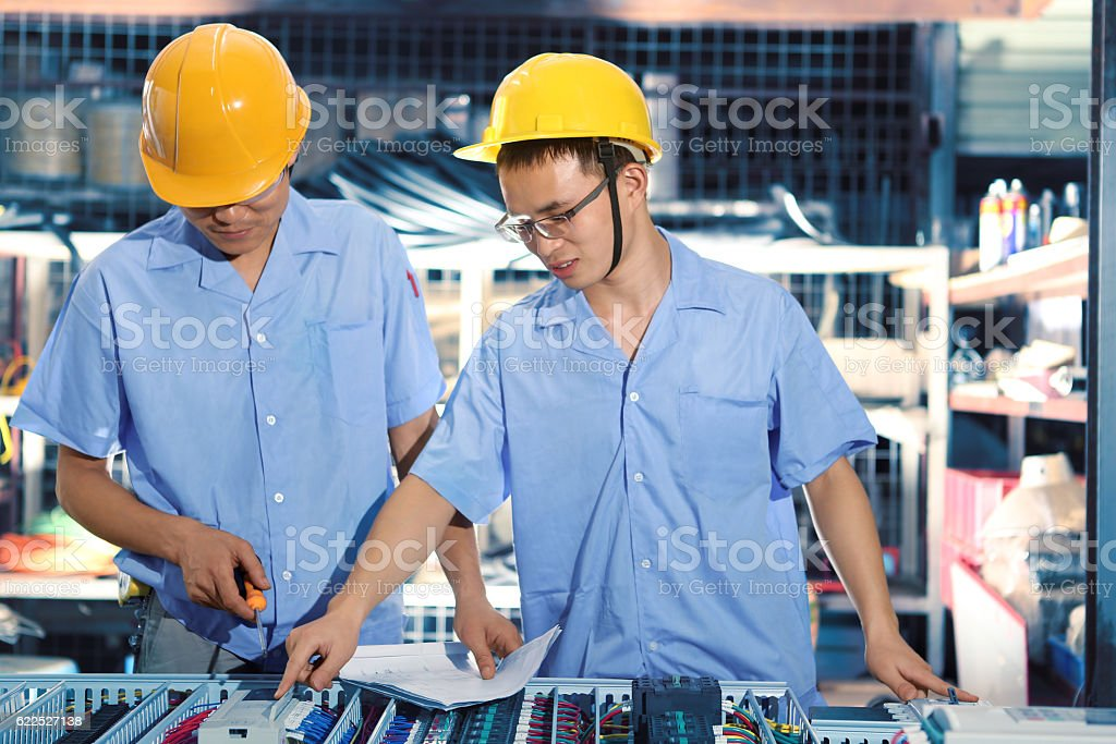 Foreman and worker reviewing blueprints in factory stock photo
