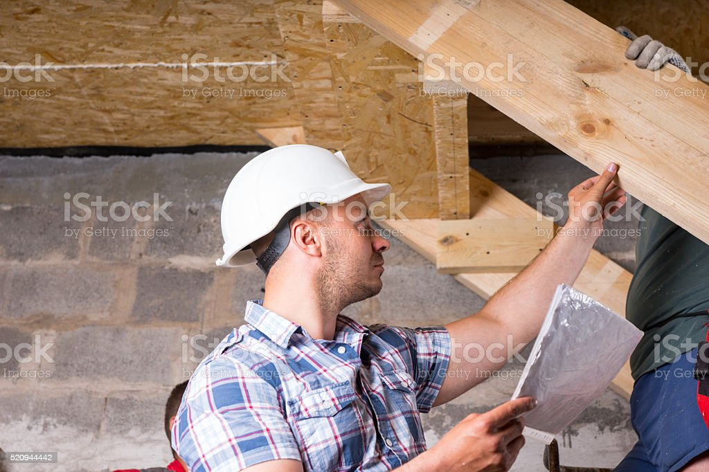 Foreman Inspecting Work on Staircase in New Home stock photo