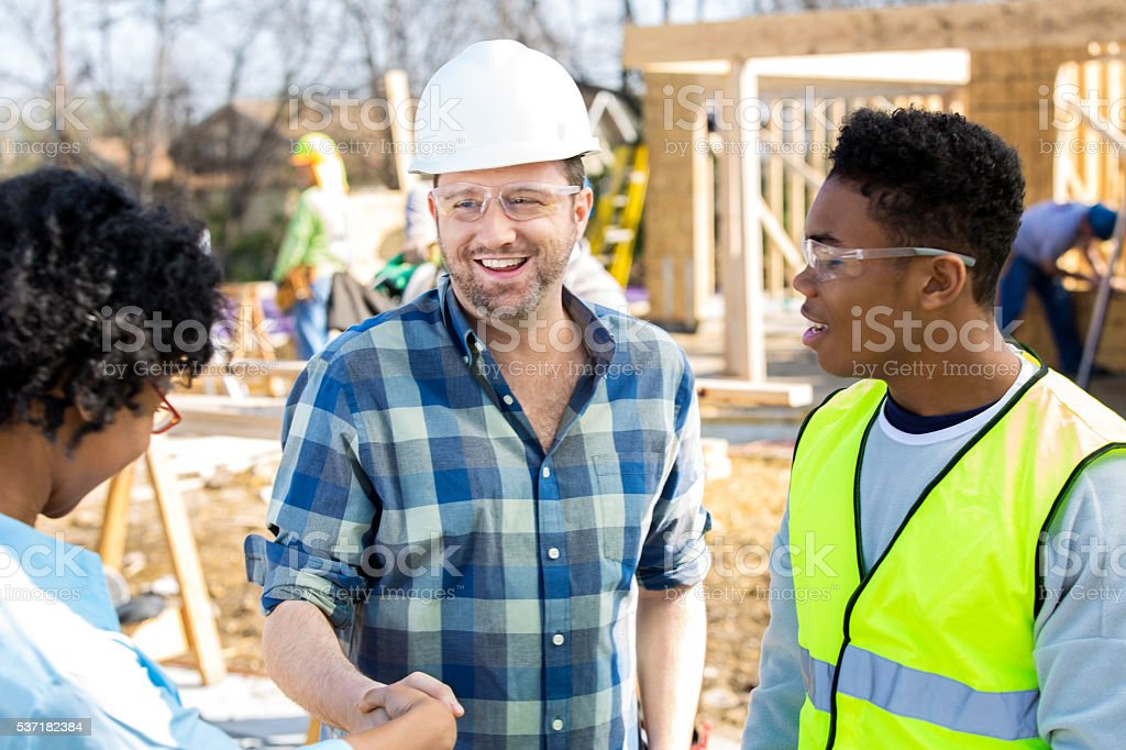 Foreman updates home builder at job site stock photo