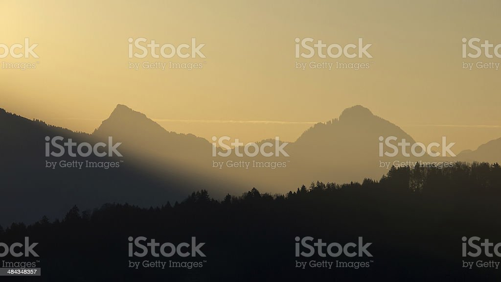 Forest and mountain silhouettes at sunrise stock photo