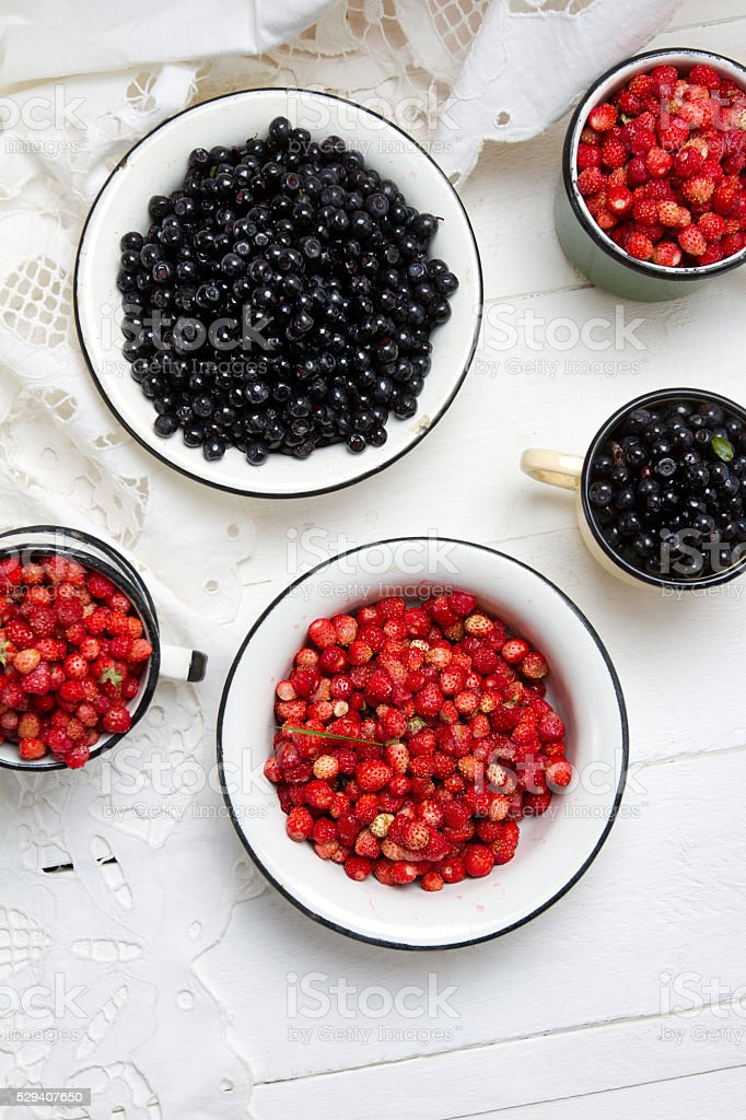 Forest berries: strawberries and blueberries in old bowls stock photo