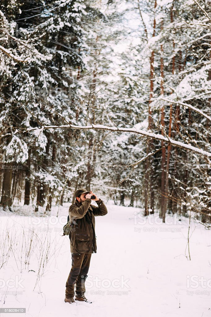 Forest Hiker Looking Through Binoculars In A Deep Winter Forest stock photo